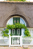 Traditional and quaint thatched cottage house and white picket fence on Fano Island, South Jutland, Denmark