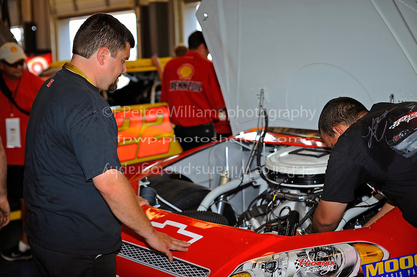 The crew at work on the Phoenix Racing #51 in the garage.