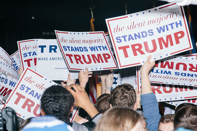 People in the audience pass signs around before real estate mogul and Republican presidential candidate Donald Trump speaks at a rally at Exeter Town Hall in Exeter, New Hampshire, on Thurs., Feb. 4, 2016.