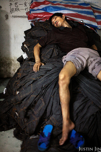 """A worker takes a dawn break on a pile of jeans after scrubbing jeans all night using a sanding machine in Mr Huang's factory in Zhongshan city, China..This picture is part of a photo and text story on blue jeans production in China by Justin Jin. .China, the """"factory of the world"""", is now also the major producer for blue jeans. To meet production demand, thousands of workers sweat through the night scrubbing, spraying and tearing trousers to create their rugged look. .At dawn, workers bundle the garment off to another factory for packaging and shipping around the world..The workers are among the 200 million migrant labourers criss-crossing China.looking for a better life, at the same time building their country into a.mighty industrial power."""