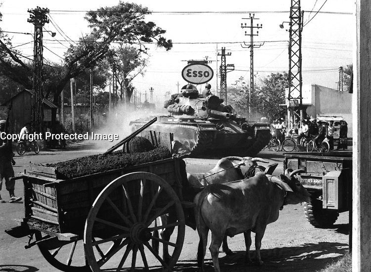 Tank from 1st Bn., 69th Armor, 25th Inf. Div., moves through Saigon shortly after disembarking from LST at Saigon Harbor, March 12, 1966.  SP/5 Park, USA.  (USIA)<br /> NARA FILE #:  306-MVP-25-1<br /> WAR &amp; CONFLICT BOOK #:  419