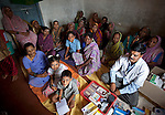21 May 2013, Mandiganal Village, Karnartaka, India:  Villages wait patiently to be attended to by Dr Bellada of the Karnataka Mobile Health Clinic project in the Anganwadi centre at Mandiganal Village outside of Hubli. The World Bank is financing the Karnataka Health Systems Project that is bringing mobile health clinics to remote villages in Karnataka and covers the cost of an ambulance, a doctor, pharmacist, two nurses, a cleaner and a driver. Villagers have the opportunity to see a doctor once a week for basic services and will be referred to Primary Health Care centres for larger issues Picture by Graham Crouch/World Bank