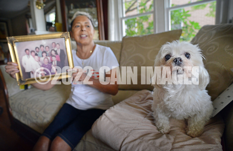 Miriam Rodriguez, of Bethlehem, Pennsylvania holds a family portrait that includes her brother Frank Rodriguez in her living room as her dog Roman, seniors at a photographer Tuesday, September 26, 2017 in Bethlehem, Pennsylvania. Frank Rodriguez -- who was in state prison for violating parole (smoking marijuana) on a felony (theft of a $1 lemonade) -- was on death vigil in prison for 10 weeks before finally being granted compassionate release. He died a day and a half later. (WILLIAM THOMAS CAIN / For The Philadelphia Inquirer)