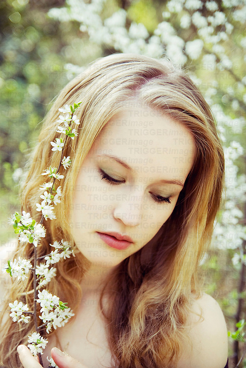 Close portrait of young woman with wavy hair and spring flowers looking down to the side
