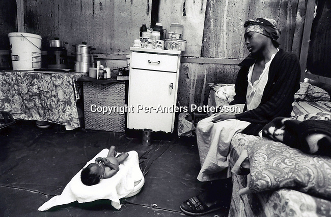 KHAYELITSHA, SOUTH AFRICA - SEPTEMBER 18:  Nozuko Dlala, age 28, cries as a nurse prepares to take her 6-month old daughter to hospital on September 18, 1999 in Kahyelitsha, a the biggest township outside Cape Town, South Africa. Nozuko and her baby are both infected with HIV. Its estimated that about one thousand South African's are infected a day and that about five million of the population are infected. .Photo: Per-Anders Pettersson/ Agentur Focus......