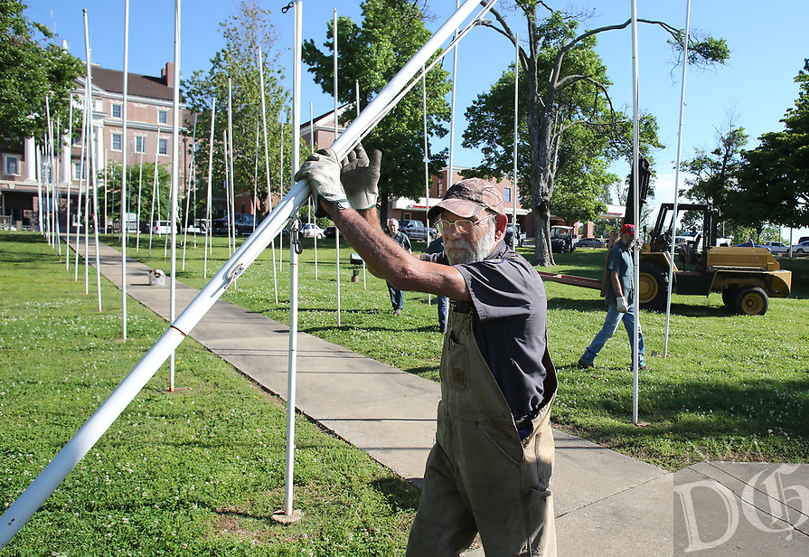 NWA Democrat-Gazette/DAVID GOTTSCHALK  Dennis Moore, with engineering at Veterans Health Care System of the Ozarks, positions Monday, May 15, 2017, one of 101 flag poles on the campus in Fayetteville. The flag poles will be used as part of the ceremonies for the arrival of the half scale replica of the Vietnam Memorial Wall. The replica will be on the campus from May 18-22.