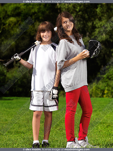Portrait of two smiling children, brother and sister, 10 and 13, practicing baseball, active summer outdoor lifestyle.