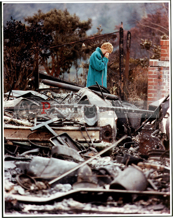 A woman weeps while standing in the charred remains of her home after the 1989 Oakland Firestorm. Over 3000 homes were destroyed in the blaze that left entire sections of the Oakland, Calif., hills looking like a moonscape.  (Alan Greth)