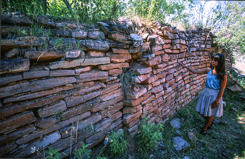 DR NIEVES ZEDENO STANDS NEXT TO THE REMAINING ENTRY WAY WALL OF GRASSHOPPER PUEBLO FOUND TODAY NEAR WHITERIVER ARIZONA, HOME TO THE WHITE MOUNTAIN APACHE INDIAN TRIBE