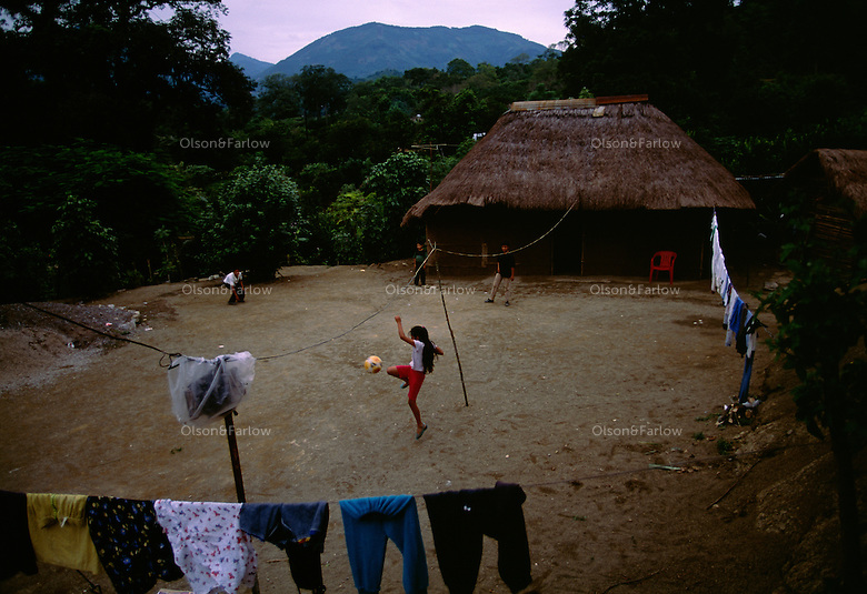 "Children play in the courtyard in front of their traditional thatched-roof adobe home in Palictla, Mexico. South of Ciudad Valles the road passes through Huasteca Indian country. At one time the Huastec population was once estimated to be one million, but today they number about 150,000. <br /> Families in this tropical region are orange pickers. The family of Hipolito Marcial, includes seven children. He built his house 12 years ago--the thatch called ""zacate"" grass will last around 20 years before it must be replaced."