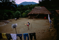 Children play in the courtyard in front of their traditional thatched-roof adobe home in Palictla, Mexico. South of Ciudad Valles the road passes through Huasteca Indian country. At one time the Huastec population was once estimated to be one million, but today they number about 150,000. <br /> Families in this tropical region are orange pickers. The family of Hipolito Marcial, includes seven children. He built his house 12 years ago--the thatch called &quot;zacate&quot; grass will last around 20 years before it must be replaced.