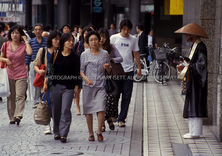 7/7/2000--Tokyo, Japan..A Buddhist monk prays and collects alms outside Shinjuku Station, Tokyo's busiest train station....All photographs ©2003 Stuart Isett.All rights reserved.This image may not be reproduced without expressed written permission from Stuart Isett.