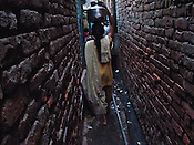 A young woman carries water in her in her slum in Govind Puri, New Delhi, India.