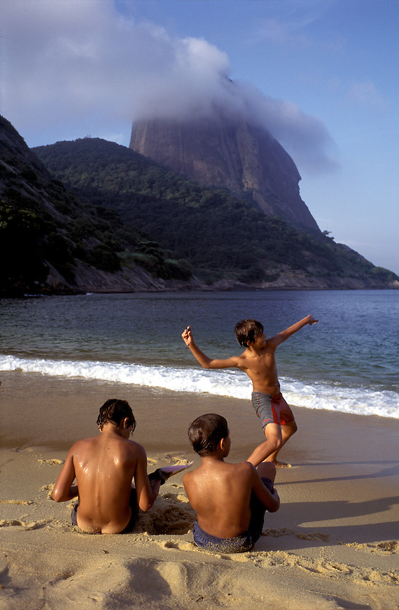 Three carioca boys toss stones into the ocean below a cloud-shrouded Sugarloaf on Rio's Red Beach. Winding along the narrow littoral between mountains and sea, Rio is set in one of the world's most beautiful places.