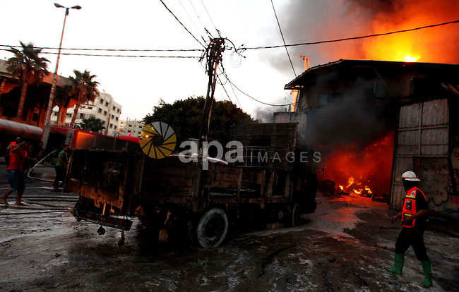 Palestinian firefighters try to extinguish fire from  soap factory that caught fire moments after it was hit by an Israeli airstrike in Gaza City August 10, 2014. Palestinian and Israeli negotiators on Sunday said they had accepted an Egyptian proposal for a new 72-hour truce with Israel, clearing the way for a possible resumption of talks on a long-term cease-fire arrangement in the Gaza Strip. Photo by Ashraf Amra