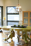 The dining table in  Meg and David Miller's house in Hilltop--a bright apple green table, a classic glass chandelier, and modern chairs is a mix of old and new.