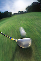 Golf course on Long Island, New York. Golf club striking ball on fairway, close-up, blurred motion.