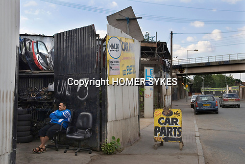 East London Lea Valley  site of the 2012 Olympic Games village and arena, Chapman Road E9 , Stratford, England 2007. Unit 5 Man waiting fro his car to be repaired.