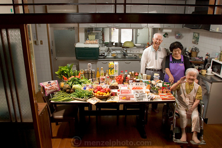 """(MODEL RELEASED IMAGE).The Matsuda family in the kitchen of their home in Yomitan Village, Okinawa, with a week's worth of food. Takeo Matsuda, 75, and his wife Keiko, 75, stand behind Takeo's mother, Kama, 100. The couple's three grown children live a few miles away. Hara hachi bu: """"eat only until 80 percent full,"""" say older Okinawans. The island has been the focus in recent years of researchers trying to discover why a disproportionately large number of Okinawans are living to age 100 or more. (From the book Hungry Planet: What the World Eats)"""