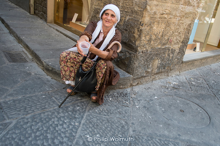 Roma woman begging in the street, Florence, Italy