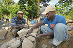 Ernst Beouchamp (left) and Saintorick Joseph place stones in the foundation of a house being built by Church World Service for a family that lost their home in Lareserve, a village near Jean-Rabel in northwestern Haiti, during Hurricane Matthew in 2016.  <br /> <br /> CWS is a member of the ACT Alliance.
