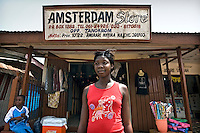 A young woman stands in front of a shop called the Amsterdam Store in Berekum. Many shop owners in this town have shops named after European cities refering to the fact that they have spent time there and come back with enough capital to start a business.