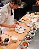 USA, California, Los Angeles, chef decorating a cheese plate at the cheese bar of Comme Ca Restaurant.