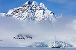 Norway, Svalbard, sail boat Arctica anchored at edge of fjord ice in front of glacier and high mountain