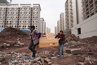 Two Women Carrying A Box Out Of A Residential Real Estate Development In Chongqing, China.  © LAN