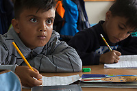 """Serbia. Vranje is a city and the administrative center of the Pčinja District in southern Serbia. «Svetozar Markovic » Elementary School. Classroom.1st Grade. Drawing class. Two young Afghan boys, both refugees, are taking notes in Serbian language. The Pestalozzi Children's Foundation (Stiftung Kinderdorf Pestalozzi) is advocating access to high quality education for underprivileged children. It supports in Vranje a project called"""" Education for child rights"""". 17.4.2018 © 2018 Didier Ruef for the Pestalozzi Children's Foundation"""