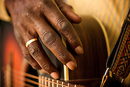 An african-american blues musician rests his hand on his acoustic guitar