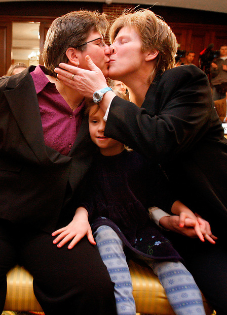 Dawn BarbouRoske, left, of Iowa City kisses her partner, Jen BarbouRoske after learning of the Iowa Supreme Court ruling in favor of legalizing gay marriage in Iowa Friday in Des Moines.  Between them is thier daughter Bre, 6.