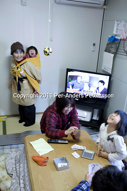 RIKUZENTAKATA, JAPAN - DECEMBER 4: Earthquake and Tsunami survivor Sasaki Honami (r) , age 7, plays cards with her mother and father as her grandmother carries her little sister Sasakai Tonami in their small flat in a temporary housing complex on December 4, 2011, in Rikuzentakata, Japan. Northeastern Japan's coastline was struck by an earthquake measuring 9.0 on the Richter scale and a Tsunami on March 11, 2011 which destroyed villages and livelihoods for hundreds of thousands of people. Almost 16,000 dead, thousands missing, more than 700,000 properties destroyed and an estimated 387,000 survivors lost their homes. Its estimated that it will take more than five years to rebuild. The cost is estimated to 309 billion U.S. dollars, the world's most expensive natural disaster. Many children suffered especially with school destroyed, education interrupted and the loss of family members took a heavy toll. (Photo by Per-Anders Pettersson)