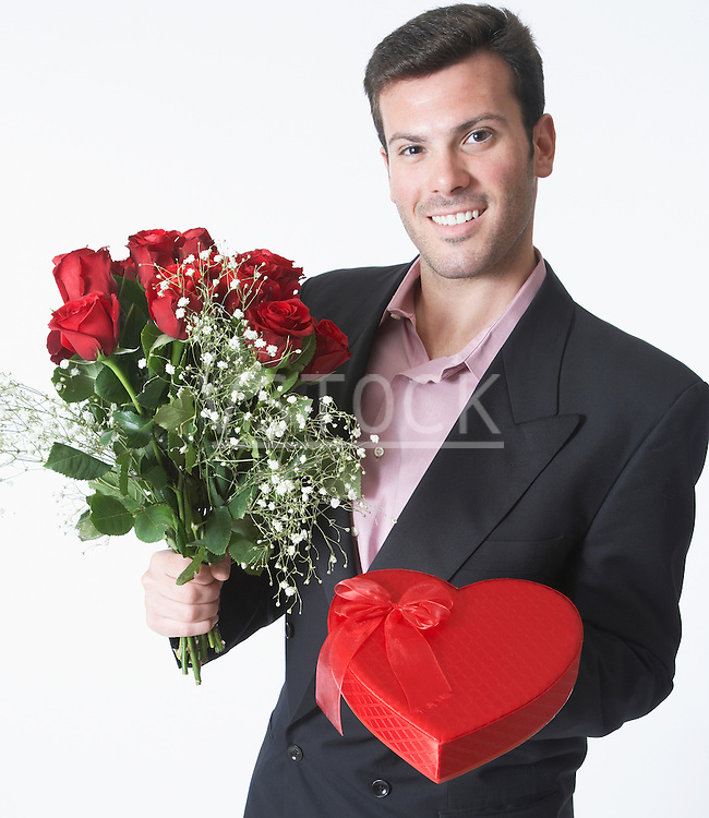 Man holding bouquet and Valentine's gift, portrait