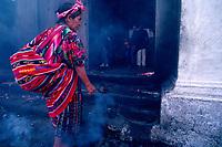 Guatemala, Chichicastenango, woman shaking smoking incense  in front of church of Saint Thomas