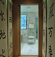 Cedar wood cupboards line the entrance to the bathroom and hand-painted Japanese characters decorate the white banners which serve as doors