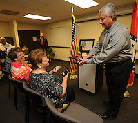 NWA Democrat-Gazette/ANDY SHUPE<br /> Cpl. Sid Ramirez (left) of the University of Arkansas Police Department, presents the the American Police Hall of Fame Medal of Honor Wednesday, Sept. 2, 2015, to Myrrah Mueller of Farmington (center) as her children Paula Mueller and John Mueller, both of Prairie Grove, during a ceremony at the University of Arkansas Police Department in Fayetteville. Myrrah Mueller's husband, West Fork Police Chief Paul Mueller, was shot and killed on March 20, 1981, while making a traffic stop in West Fork following a robbery in Fayetteville.