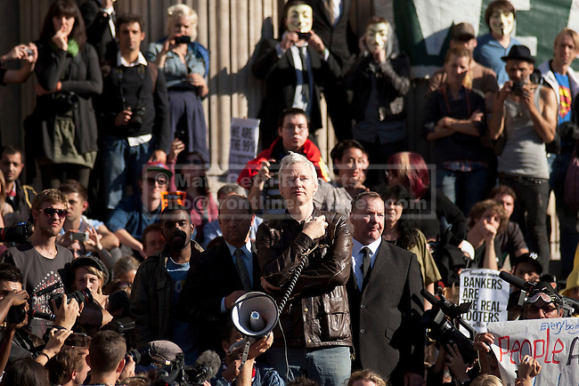 15/10/2011. LONDON, UK. Julian Assange stands on the steps of St Paul's Cathedral and addresses massed protesters taking part in the Occupy London demonstration. As part of an anti-capitalist protest taking place in cities across the globe, demonstrators attempt to occupy Paternoster Square in London under the name Occupy London Stock Exchange.  After being refused entry to the square itself thousands of protesters occupied the area outside St Paul's Cathedral with some erecting tents. Credit should read: Matt Cetti-Roberts