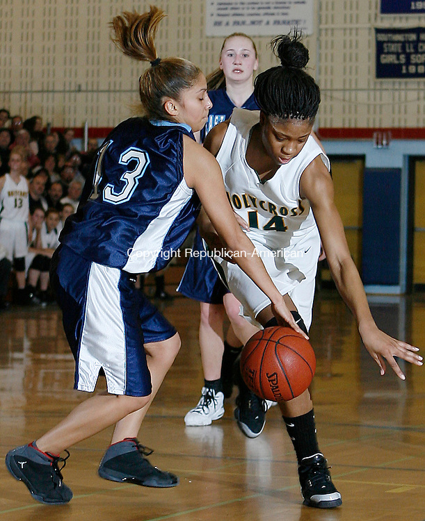 Holy Cross' Kim Clements and East Catholic's Nathalie Mastarreno battle for a loose ball in Class M semi final action at Southington High School Tuesday night.  The Crusaders proceed to the next round with their win over the Eagles 54-5  Michael Kabelka Republican / American.