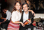 Woman and man holding a bottle of Xante cognac during the Laura Vela Spring 2014 handbag preview installation at No. 8 in New York City on September 17, 2013.