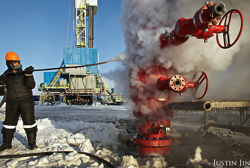 A worker sprays an Achimgaz gas drilling well to prevent it from freezing in Novy Urengoi, Siberia, Russia.