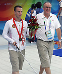 Donovan Tildesley (left) of Vancouver is helped from the podium by his father Hugh after taking the bronze medal in men's 400 metre freestyle, class S11, in the swimming finals at the Paralympic Games in Beijing, Thursday, Sept., 11, 2008.    CPC-Mike Ridewood