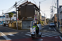 A three-wheeled delivery scooter at a crossing in Suburban Setagaya Ward,, Gotokuji, Tokyo, Japan. Friday January 11th 2019