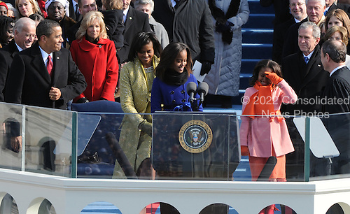 Washington, DC - January 20, 2009 -- United States President Barack Obama (L) smiles at his daughers Malia and Sasha as they head to the podium for the Obama to be sworn-in as the 44th President of the United States on the west steps of the Capitol on Tuesday, January 20, 2009.  Michelle Obama holds the bible. .Credit: Pat Benic - Pool via CNP