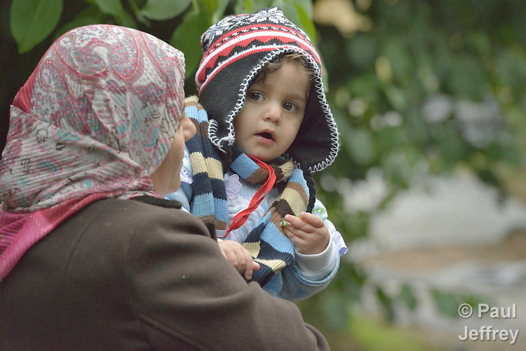 An Iraqi refugee woman holds her 18-month old daughter, Mahdi, as they approach the border into Croatia near the Serbian village of Berkasovo. Hundreds of thousands of refugees and migrants from Syria, Iraq and other countries have flowed through Serbia in 2015, on their way to western Europe.