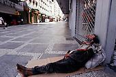 Sao Paulo, Brazil. Man sleeping rough in a city centre street - Sunday morning.