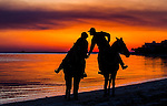 Alicia Porter and Juan Romire ride their horses down Shell Point Beach during sunset on Valentines eve.