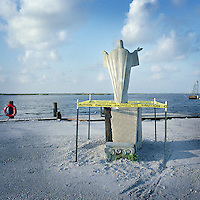 A statue of Jesus Christ faces the water at the private fishing marina in Pointe Aux Chene, Louisiana which was leased to BP as a staging ground for BP's clean up operations after the 2010 oil spill. BP employees surrounded the statue with a temporary barrier while heavy machinery operated on the grounds. The company hired local fisherman who used their own boats to skim oil from the water and deliver and lay absorbant boom in an effort to protect shorelines.