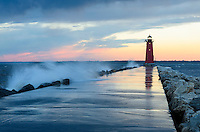 A colorful sunset and waves splashing at the Manistique Lighthouse. Manistique, MI
