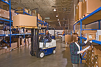 Women driving forklift and doing parts inventory at warehouse